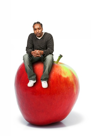 winesap apple: Black African American man sitting on a whole red delicious apple