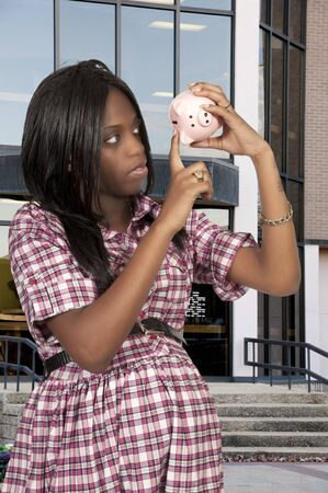 A beautiful woman holding a piggy bank full of money she has saved photo