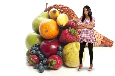 black pregnant woman: A black pregnant woman with a wide assortment of delicious and fresh fruits Stock Photo