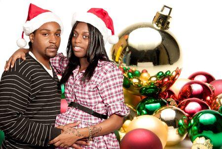 A beautiful young black couple wearing Christmas Santa Hats photo