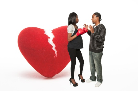 Beautiful young black pregnant woman wearing a boxing glove and a man breaking her heart photo