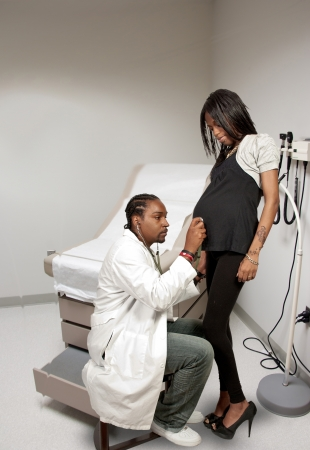 Medical doctor with a stethoscope examining a black African American Pregnant woman photo