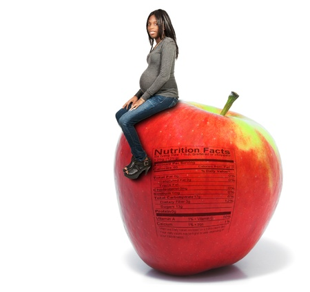 woman apple: Pregnant black woman sitting on a red delicious apple with a nutrition label
