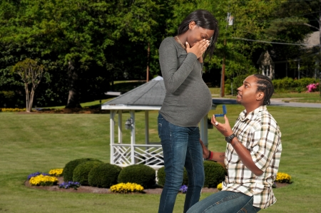 Black man proposing to a pregnant African American woman photo