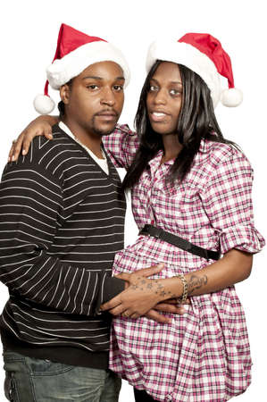 A beautiful young black couple wearing Christmas Santa Hats photo