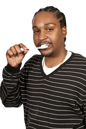 Black African American man practicing good oral dental care by brushing his teeth photo