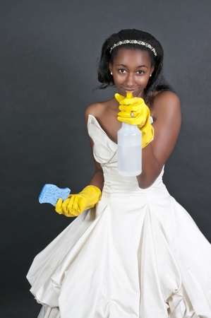 An African American glove wearing beautiful woman or maid cleaning house with a sponge and spray bottle with cleaner photo