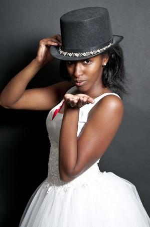 키스를 불고 웨딩 드레스와 모자에 검은 아프리카 계 미국인 여성 신부