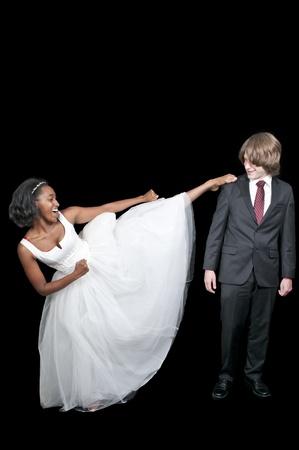 Black African American woman kicking a caucasian man. photo