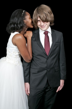 A young beautiful black African American woman whispering a secret to a young man photo