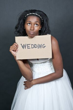 americal: Black African Americal Woman Bride in a wedding dress holding a sign Stock Photo
