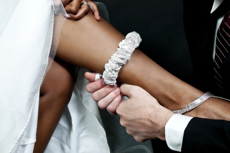 Caucasian man removing the garter from a newly married black African American woman
