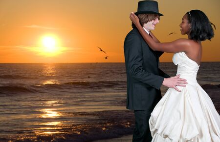 Caucasian man and a black African American woman newly married newlyweds on the beach photo