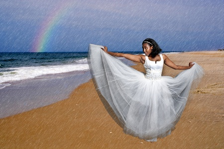 Zwarte Afrikaanse Amerikaanse Vrouw Bruid in een trouwjurk op het strand dansen in de regen