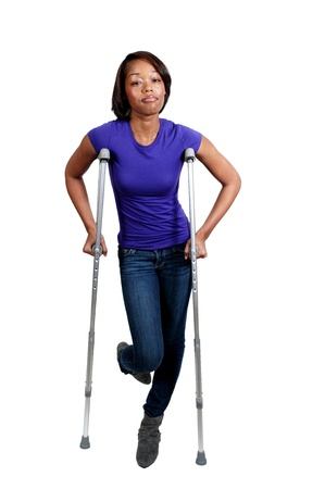 A beautiful African American black woman using a set of medical crutches to help her walk