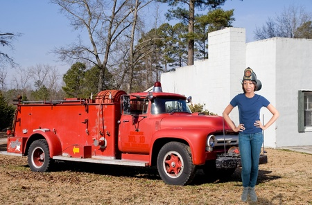antique fire truck: A beautiful woman firefighter at a fire Stock Photo