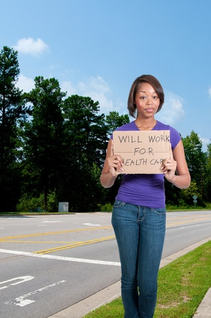impoverished: A beautiful black African American woman holding a sign that says will work for healthcare