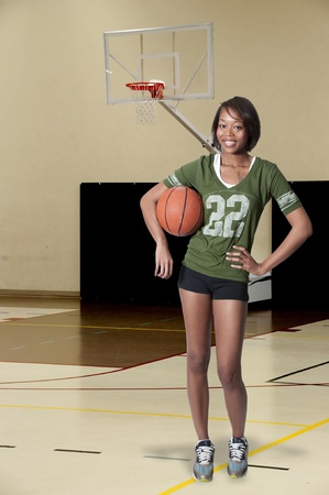 Beautiful black African American woman playing a game of basketball photo