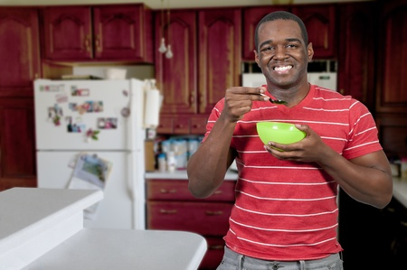Young black African American man eating food from a bowl in a home kitchen