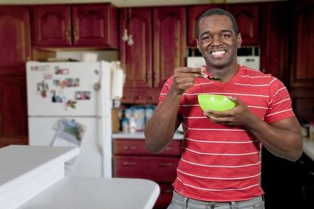 man eten: Jonge zwarte Afro-Amerikaanse man het eten van voedsel uit een kom in een huis keuken Stockfoto