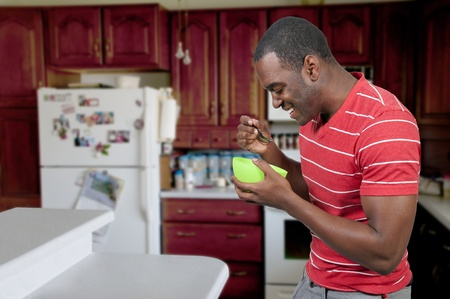 Young black African American man eating food from a bowl in a home kitchen photo