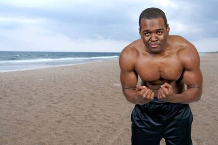 Young African American black man with his shirt removed on the beach photo