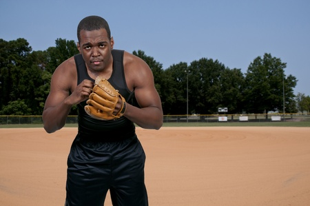 A black African American man baseball pitcher getting ready to throw a ball in a game photo