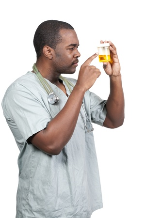 Young black African American man doctor in scrubs holding a urine sample photo