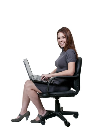 A beautiful computer savvy young woman using a laptop sitting in an office chair