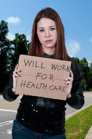 というサインを保持している美しい女性はヘルスケアのために働く