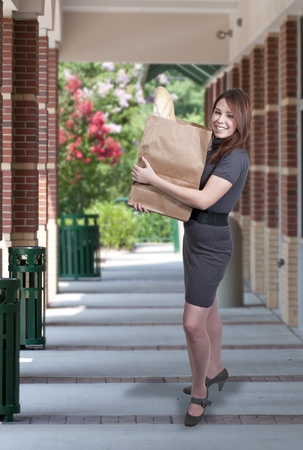 A beautiful woman grocery shopping holding a brown paper bag photo