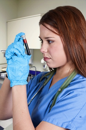 A beautiful young female doctor holding a test tube vial sample of blood Stock Photo - 12321279