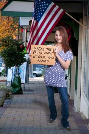 A beautiful young woman holding up a blank sign photo