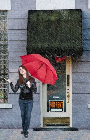 A beautiful young woman holding an umbrella in the rain photo