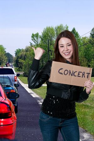A beautiful woman with a sign hitch hiking to a concert Stock Photo - 12321715