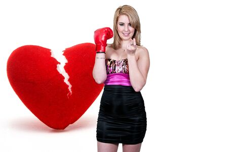 A beautiful woman in wearing a boxing glove in front of a broken heart - heartbreaker Stock Photo - 12314119