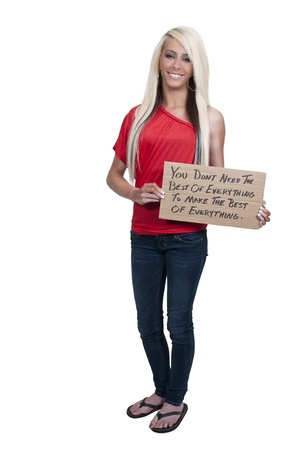 A beautiful young woman holding up a sign saying You dont need the best of everything to make the best of everything Stock Photo - 12319950
