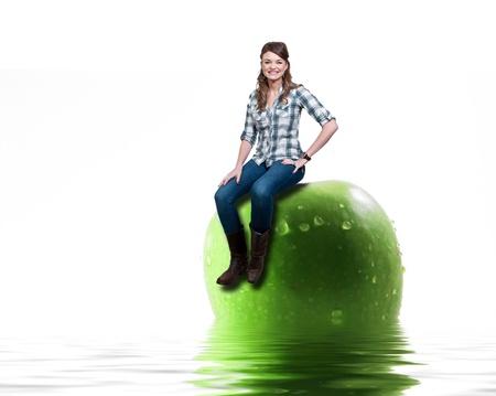水に座っている濡れているアップルの上に座って美しい女性