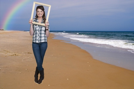 Beautiful woman looking through an ornate picture frame at the beach photo