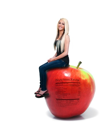 winesap apple: A beautiful young woman sitting on a whole red delicious apple with a nutrition label