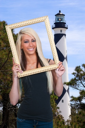 Beautiful woman looking through an ornate picture frame photo