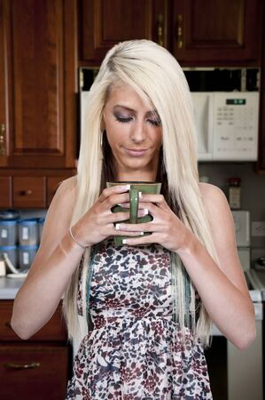 A beautiful young woman drinking and smelling coffee in her pajamas photo