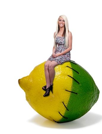 lima limon: Una hermosa mujer joven sentada en un lima lim�n Foto de archivo