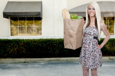 Beautiful young woman with a brown paper shopping bag photo