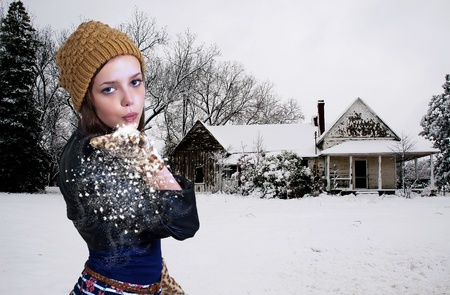 Beautiful woman blowing snow off of her hands photo