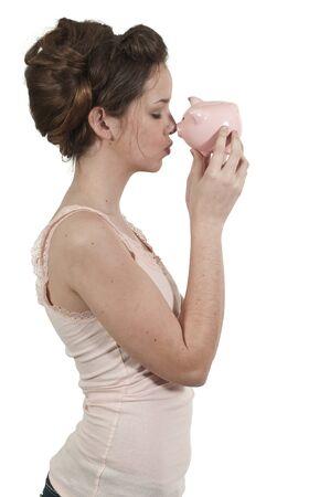 teenaged: A beautiful teenage woman holding a piggy bank full of money she has saved Stock Photo