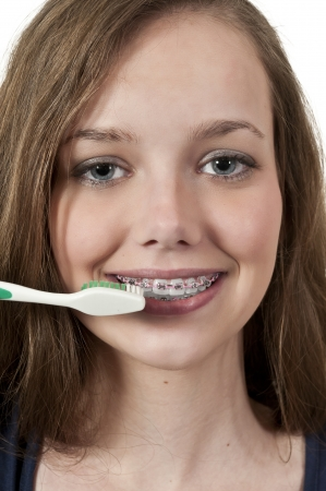 A beautiful teenage woman practicing good oral dental care by brushing her teeth Stock fotó