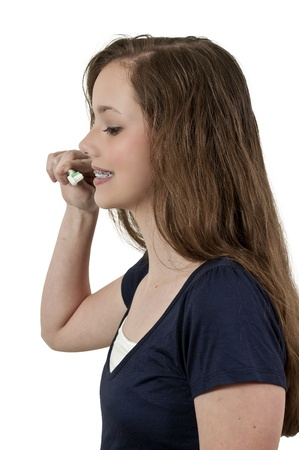 A beautiful teenage woman practicing good oral dental care by brushing her teeth photo