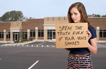 A beautiful young teenaged woman holding up a sign photo
