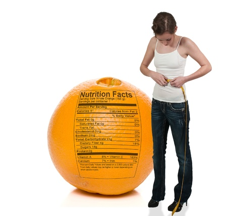 Beautiful woman measuring her waist with a tailors tape in front of an orange